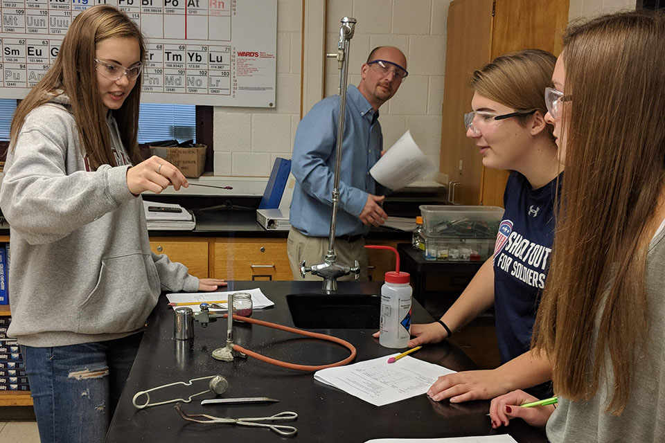 2 students watching a girl do a science chemistry experiment with teacher looking on