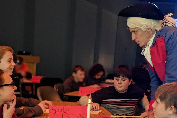 teacher dress in colonial costume speaking to kids