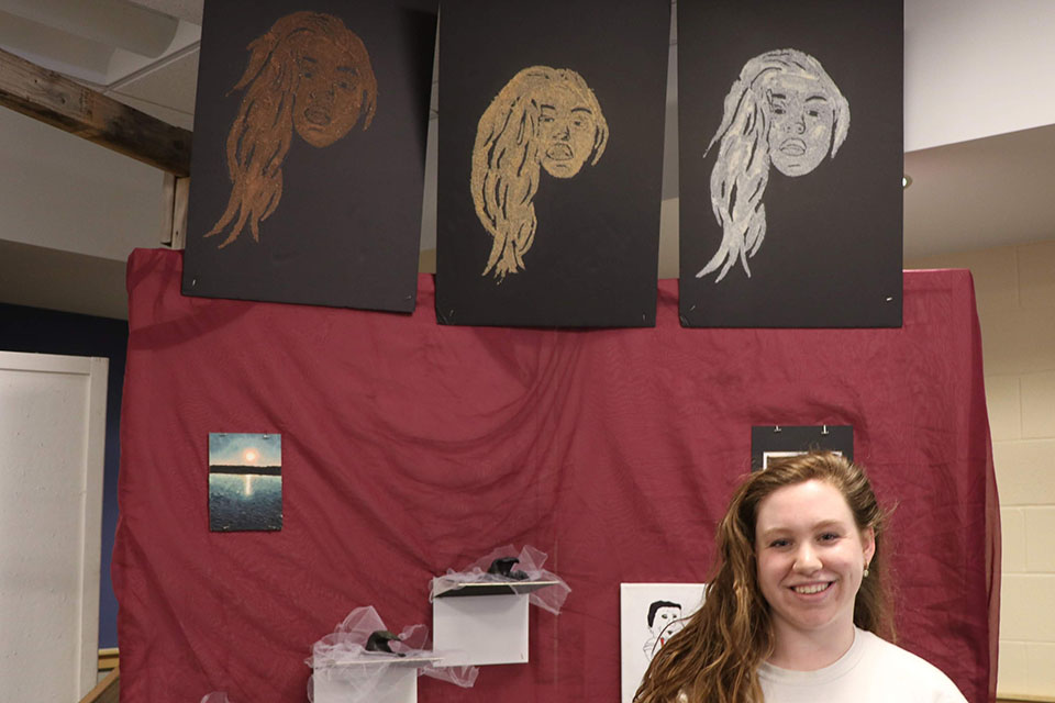 Student has three self portraits above her and which she used sand to make