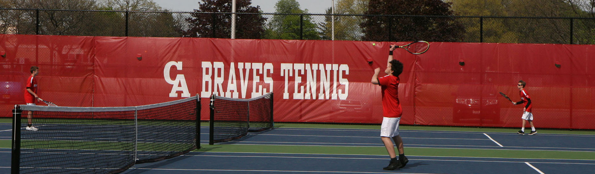 3 tennis players practicing on courts with Braves Tennis banner in background