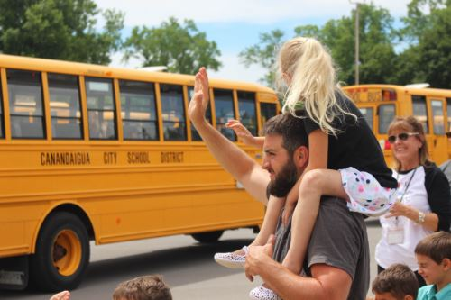 student sitting on shoulders of teacher and they are waving to the buses as they leave.