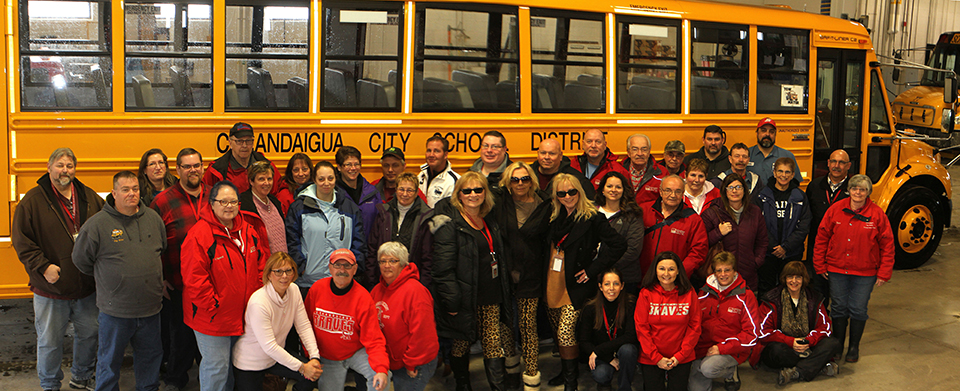 all of the school's bus drivers gathered in a group by the side of a bus posing for a picture all smiling