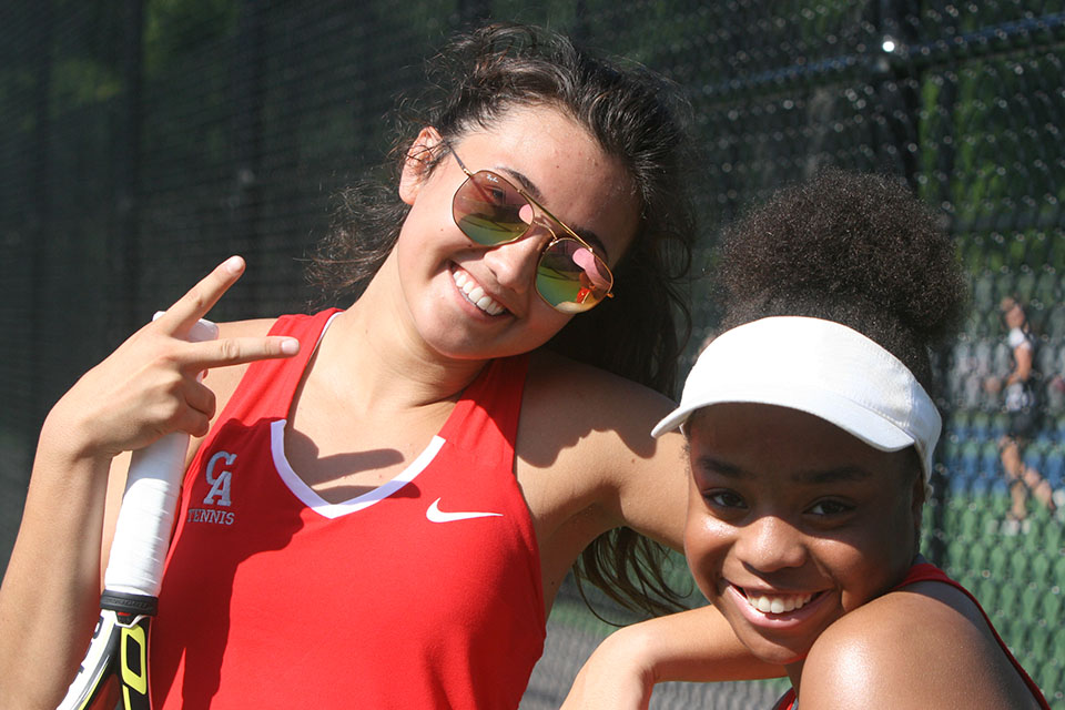 2 girls in tennis huddled together and smiling