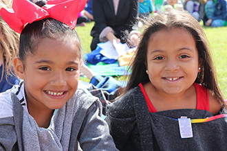 two young girls from the primary elementary school. smiling outside