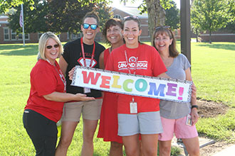 pes teachers outside holding sign that says welcome!