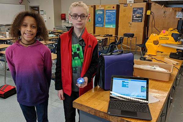 Students hold robot and have computer out in the technology classroom