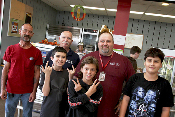 3 custodians with 3 male students in cafeteria smiling with 2 of the students giving peace sign